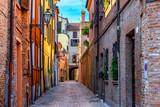 Fototapeta Uliczki - Old narrow street with arch in Ferrara, Italy.  Ferrara is capital of the Province of Ferrara