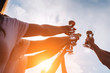 A group of girls happily raise their hands with champagne glasses in the sunset. Best friends celebrate outdoor