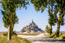 The Mont Saint-Michel Tidal Island In Normandy, France, Seen From A Dirt Road Lined With Poplar Trees In The Polders Under A Bright Sunlight.