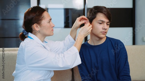 Valokuva  Woman doctor puts a hearing aid on a young guy.