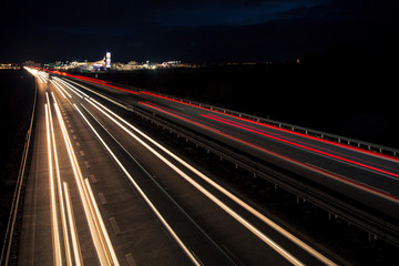 Fototapeta na wymiar Motion blurred light tracks glowing to the darkness of highway traffic to the city just after sunset. Creative long time exposure photography.