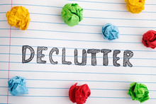The Word Declutter On Notebook Sheet With Colorful Crumpled Paper Balls Around It