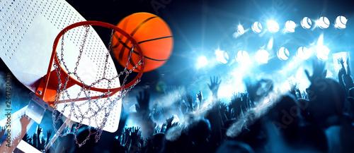 Deportes y entretenimiento. Baloncesto y deportes de equipo.Canasta  y pelota iluminados por los focos. Partido y evento deportivo. Público y multitud aplaudiendo el partido de baloncesto.