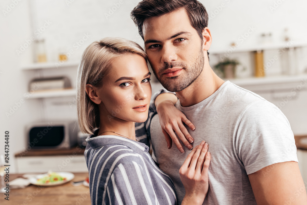 Fototapeta selective focus of handsome boyfriend and attractive girlfriend hugging and looking at camera