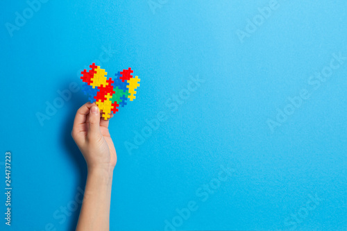 Plakaty Autyzm child-hand-holding-colorful-heart-on-blue-background-world-autism-awareness-day-concept