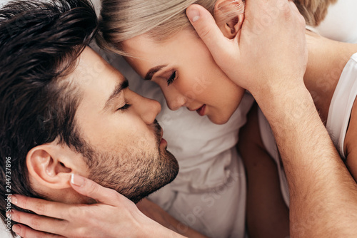 Obraz na plátne top view of of attractive girlfriend and handsome boyfriend laying in bed