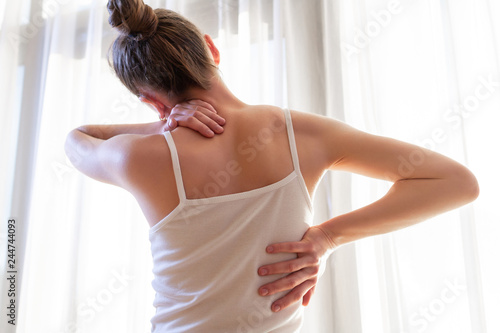 Fotografie, Obraz  Young woman suffering from neck pain and backache, stretching the muscles