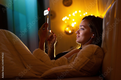 Young woman in headphones before bedtime listening to relaxing music