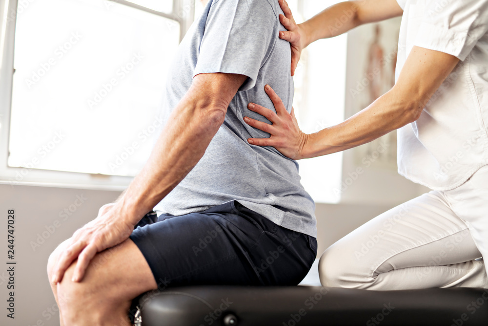 Fototapeta A Modern rehabilitation physiotherapy worker with senior client
