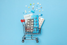 Shopping Basket And Pills In Blisters. The Concept Of Buying Drugs Online, Delivery Of Medical Devices
