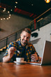 Smiling bearded freelancer mixing espresso with spoon and holding in other hand smart phone. Laptop on the table, cafeteria interior.