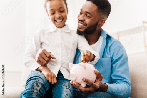 Fototapeta Girl and father putting coin into piggy bank obraz