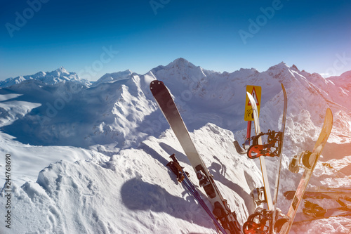 Skis and snowboards equipment standing upright in snow on background of beautiful scenery mountain massif on the North Caucasus on winter resort