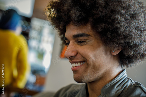 Spoed Foto op Canvas Muziekwinkel Afro american man portrait smiling in restaurant or cafe lounge.Lifestyle, diversity and social concepts.
