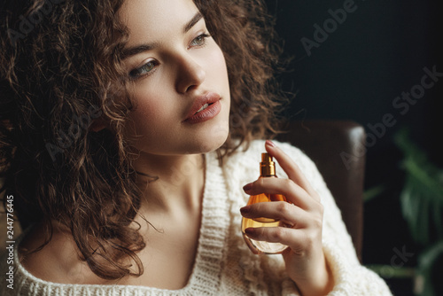 Fototapeta Close up portrait of young beautiful sensual curly woman using, holding luxury perfume in orange glass bottle. Model wearing warm winter knitted sweater. Copy, empty space for text obraz