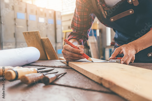 Carpenter working with equipment on wooden table in carpentry shop Fotobehang
