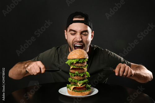 Young hungry man with cutlery eating huge burger on black background