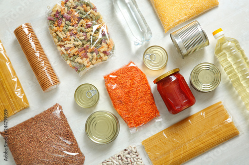 Many different products on white wooden background, flat lay. Food donation