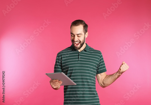 Emotional young man with tablet celebrating victory on color background - 244791242