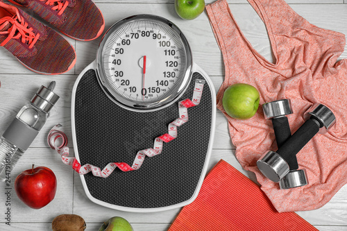 Fotografie, Tablou Flat lay composition with scales, healthy food and sport equipment on wooden background