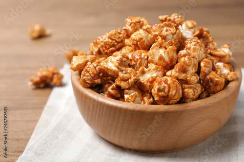 Wooden bowl with tasty caramel popcorn on table