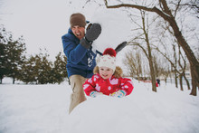 Crazy Family Screaming Dad In Warm Clothes Holding Big Snowball, Little Girl Playing With Snow In Park Or Forest Outdoors. Winter Fun, Leisure On Holidays. Love Relationship Family Lifestyle Concept.