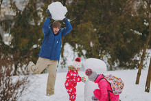 Young Family Woman, Little Girl In Warm Clothes Play Making Snowman, Crazy Man Holding Snowball In Park Or Forest Outdoors. Winter Fun, Leisure On Holidays. Love Relationship Family Lifestyle Concept.