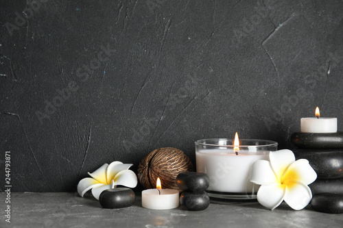 Photo  Spa composition with stones and candles on table, space for text