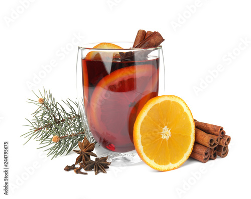 Glass of mulled wine with fir branch, cinnamon and orange isolated on white