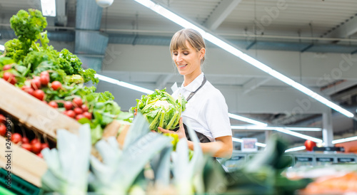 Obraz na płótnie Woman working in a supermarket sorting fresh fruit and vegetables