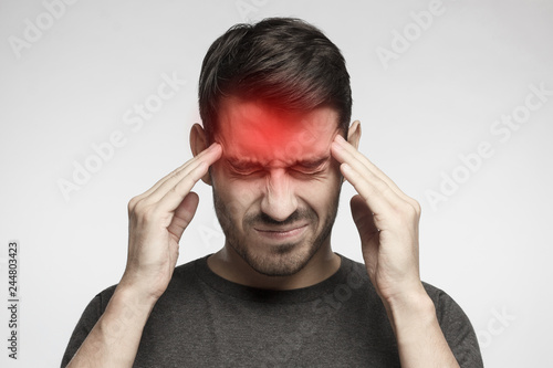 Fotografering Portrait of young man isolated on gray background, suffering from severe headach