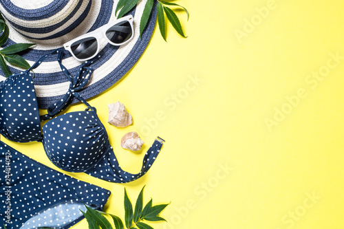 Fotografie, Obraz  Woman summer beach cloth set - hat, swimsuit and sunglasses on yellow top view
