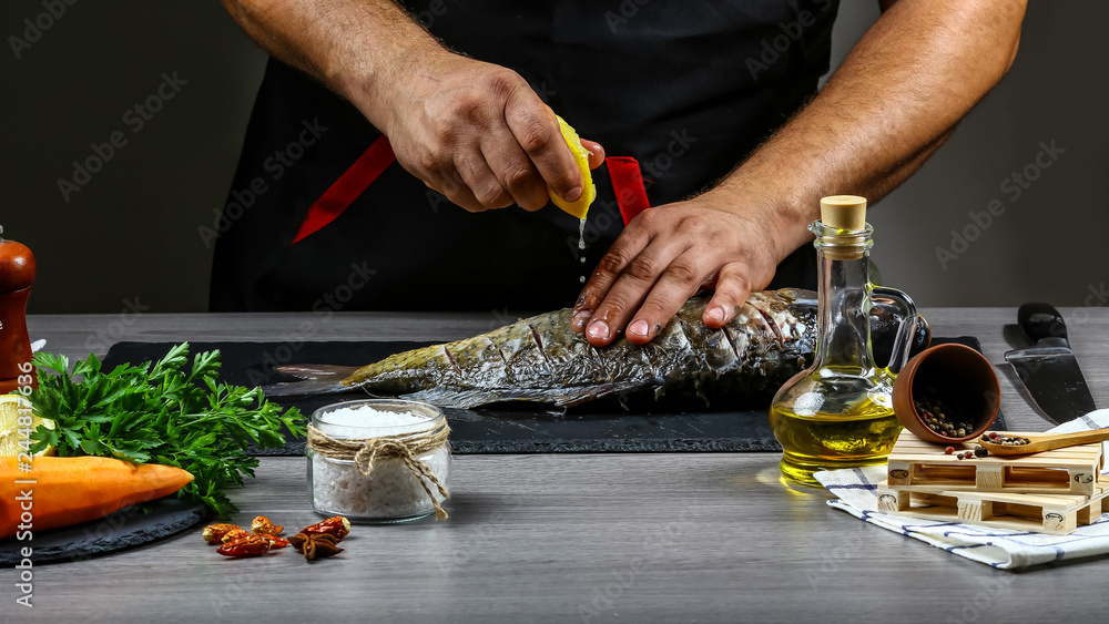 Fototapety, obrazy: Add lemon juice to fish carp in chef hands, black background. Food recipe photo, copy text