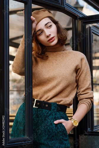 Outdoor portrait of young beautiful fashionable woman wearing beige beret, turtleneck sweater, black suede belt, green corduroy high waisted trousers, golden wrist watch