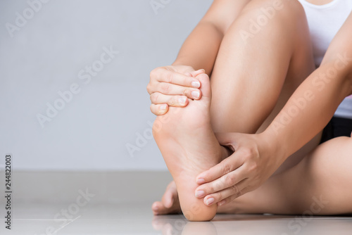 Fotografía  Closeup young woman feeling pain in her foot at home