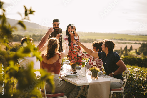 Fotografia  Group of people toasting wine during a dinner party