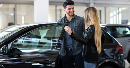 Obraz na PlexiYoung couple choosing new car for buying in dealership shop