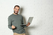 Emotional Young Man With Laptop Celebrating Victory Near Brick Wall. Space For Text