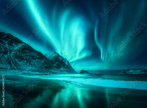 Foto op Canvas Nachtblauw Amazing aurora borealis. Northern lights in Lofoten islands, Norway. Starry sky with polar lights. Night winter landscape with aurora, sea with frosty coast and sky reflection, snowy mountains. Travel