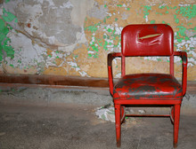 A Bright Red Vinyl Midcentury Chair With Slashed Back, Worn Seat And Rusted Arms And Legs On A Dirty Grey Epoxy Floor With A Wall Covered In Peeling Lime Green, Gold And White Paint In The Background.