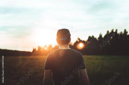 Fotografia  A man looks at the shadow of the sun. Photo in dark key.