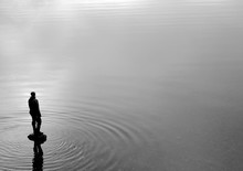 Black & White Photo Of A Fisherman In Silhouette Standing On A Rock In An Empty Lake - With Gentle Ripples Cascading Across Shallow, Still Water During An Early Winter Morning In The Pacific Northwest