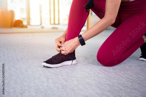 Fotografía  Young woman in good shape tying shoes at gym