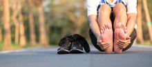 Young Fitness Man Holding His Sports Leg Injury. Muscle Painful During Training. Asian Runner Having Feet Sole Ache And Problem After Running And Exercise Outside Morning. Sport And Healthy Concepts