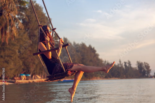 Poster Naufrage Young beautiful happy woman swinging on a swing on the beach during sunset, relaxing travel lifestyle concept