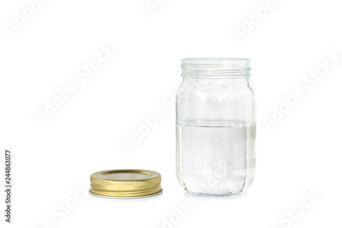 Water into jar of golden cap is open on a white background.
