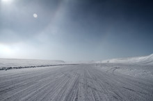 An Ice Road Leading Towards Snow Covered Hills With A Partial Sundog Located Near The Community Of Cambridge Bay, Nunavut, Canada