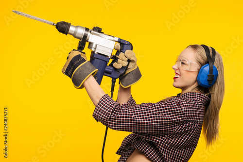 Beautiful young woman in goggles and headphones worth holding perforator drill isolated on yellow background