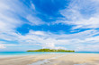 Idyllic white sand beach seascape blue sky with island