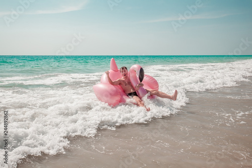 Cuadros en Lienzo A man is having fun on pink flamingo inflatable pool float in the turquoise sea